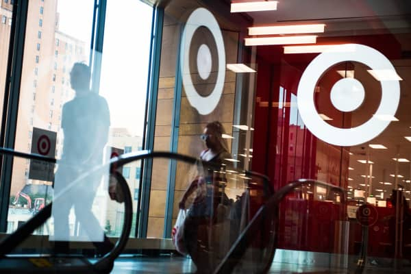 Pedestrians walk past the Target logo reflected in a window at City Point in Brooklyn, New York.