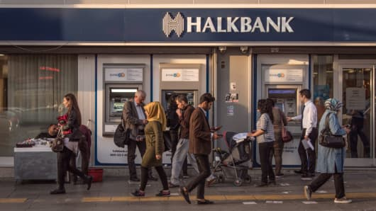 People pass in front of a HalkBank branch in central Ankara, Turkey, on 23 Oct. 2017.