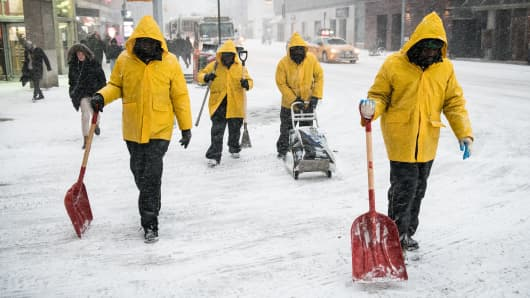 Workers carry shovels while crossing a street near Union Square during a snow storm in New York, U.S., on Thursday, Jan. 4, 2018.