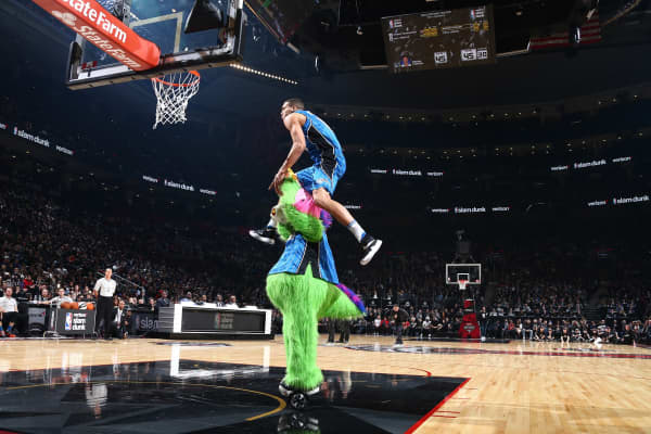 Aaron Gordon of the Orlando Magic dunks over Stuff the Magic Dragon, the mascot of the Orlando Magic, during the Verizon Slam Dunk Contest in 2016