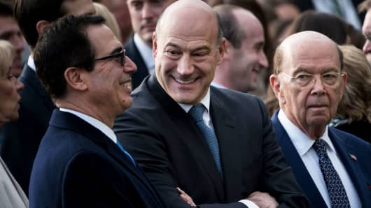 Secretary of the Treasury Steven Mnuchin (L), National Economic Council Director Gary Cohn (C) and US Secretary of Commerce Wilbur Ross wait for President Donald Trump to speak about newly passed tax reform legislation during an event at the White House December 20, 2017 in Washington, DC.