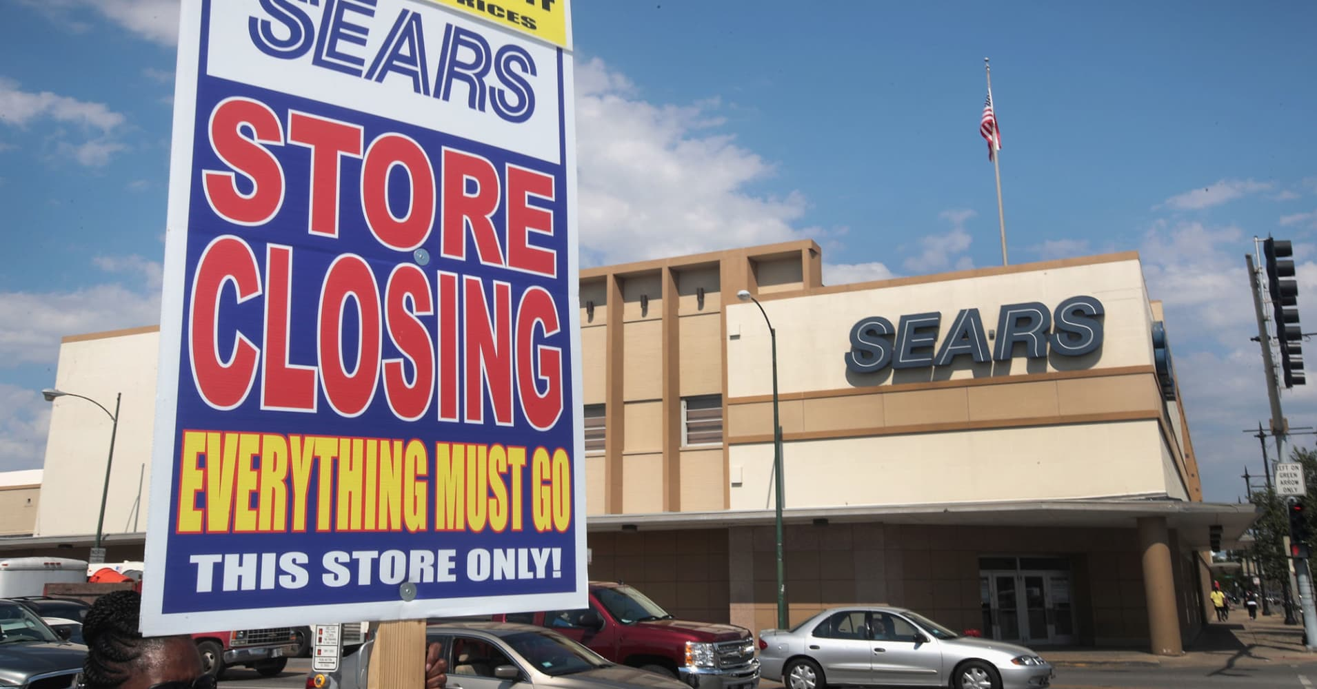 A worker holds a sign announcing a store-closing sale outside the 60-year-old Sears store in Chicago.