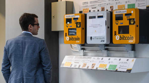 A man looks at ATM machines (L and R) for digital currency Bitcoin in Hong Kong on December 18, 2017.
