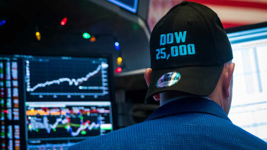A trader wears a DOW 24,000 hat as he works on the floor of the New York Stock Exchange, (NYSE) as the Dow Jones Industrial Average crosses 25,000 on Jan. 4ht, 2018 for the first time.