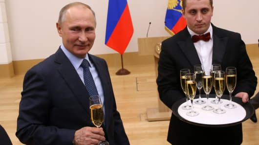 Russian President Vladimir Putin holds a glass of champagne in Moscow, Russia.