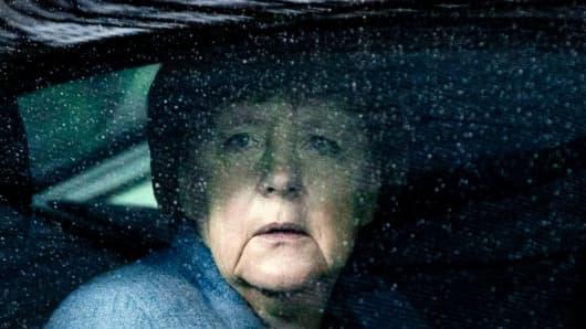 German Chancellor Angela Merkel looks through raindrops on her car window.