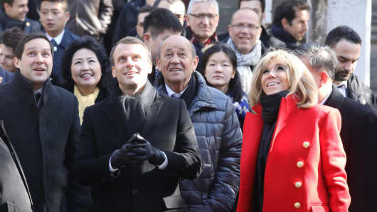 French President Emmanuel Macron (centre L) and his wife Brigitte Macron (centre R-red coat) are given a tour during a visit to the Great Mosque of Xian in the northern Chinese city of Xian on January 8, 2018. Macron on January 8 launched a state visit to China in Xian -- the starting point of the ancient Silk Road -- in a nod to his counterpart's scheme to revive the famous trading route.