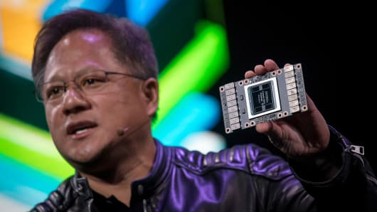 Jen-Hsun Huang, president and chief executive officer of Nvidia Corp., holds a Nvidia Volta 125 Teraflops per second (TFLOPS) Tensor Core as he speaks during an event at the 2018 Consumer Electronics Show (CES) in Las Vegas, Nevada, U.S., on Sunday, Jan. 7, 2018.