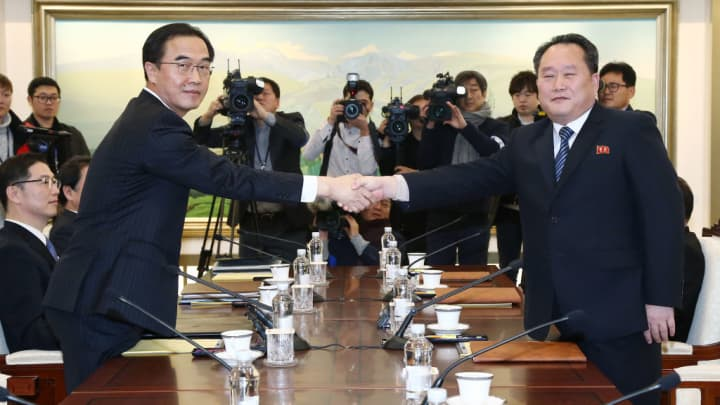 Cho Myoung-gyon, South Korea's unification minister, left, and Ri Son Gwon, chairman of North Korea's Committee for the Peaceful Reunification of the Fatherland, shake hands while posing for photographs during a meeting in the village of Panmunjom in the Demilitarized Zone (DMZ) in Paju, South Korea, on Tuesday, Jan. 9, 2018.