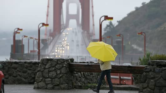 A woman walks in the rain at a vista point with the Golden Gate Bridge in the background Monday, Jan. 8, 2018, near Sausalito, Calif. Storms brought rain to California on Monday and increased the risk of mudslides in fire-ravaged communities in devastated northern wine country and authorities to order evacuations farther south for towns below hillsides burned by the state's largest-ever wildfire.