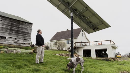 A customer inspects a solar panel that is linked to a Tesla Motors Powerwall at a home in Monkton, Vermont.