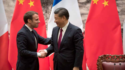 French President Emmanuel Macron (L) and Chinese President Xi Jinping shake hands after a joint press briefing at the Great Hall of the People in Beijing on January 9, 2018.