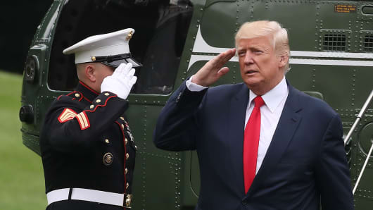 President Donald Trump salutes a US Marine after landing on the South Lawn at the White House.
