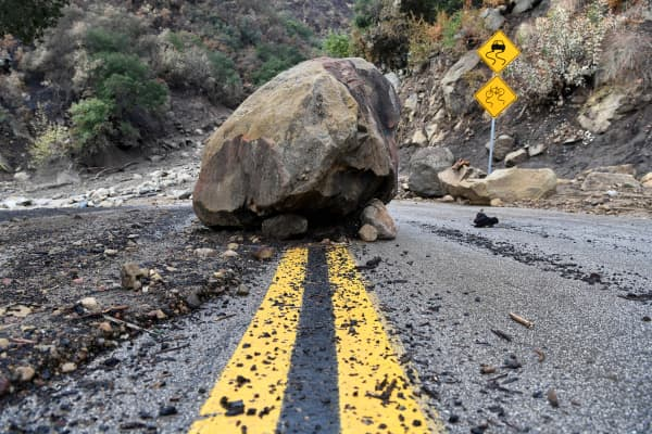 A large boulder sits in the middle of Bella Vista Drive in Montecito, Calif., following the rain storm, Tuesday, Jan. 9, 2018.