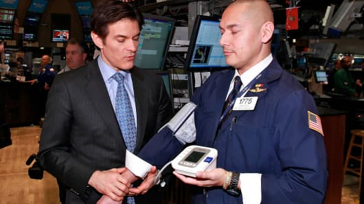 Dr. Mehmet Oz takes blood pressure of trader Mark Otto at New York Stock Exchange on February 7, 2011 in New York City.
