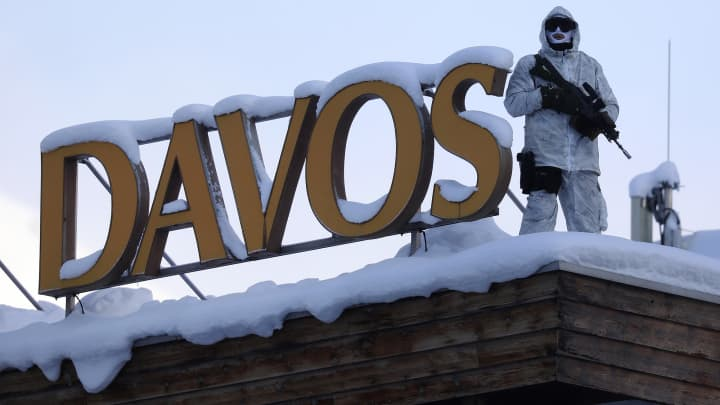 An armed member of the Swiss Police watches from the roof of the Hotel Davos ahead of the World Economic Forum (WEF) in Davos, Switzerland, on Monday, Jan. 16, 2017.