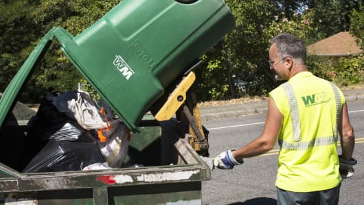 A worker empties garbage from a Waste Management trash bin in Seattle.
