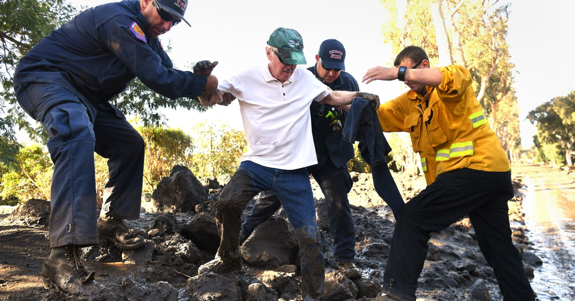 Firefighters from left, Mark Todd, John Cecena and Jeff Shea help Birmawood Country Club resident Terry Connery escape his home after a major storm hit the burn area Wednesday on January 10, 2018 in Montecito, California.