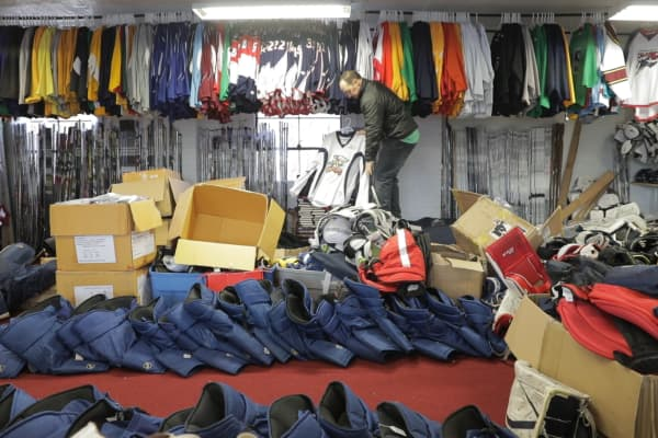 Eric Fanelli pulls down a used practice jersey he's sold on Sideline Swap from his Rocky Hill, Connecticut warehouse.