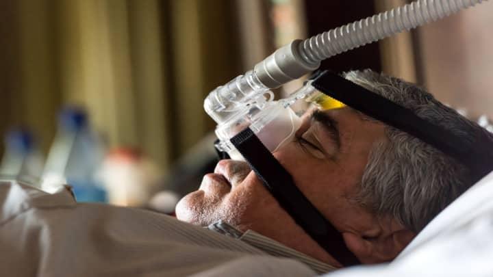 Man sleeping, using a mask for apnea sleep disorder treatment.