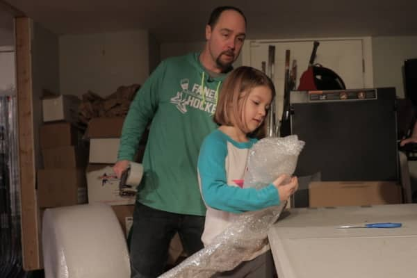 Fanelli and his daughter work together in his basement to pack up a hockey stick he's sold.