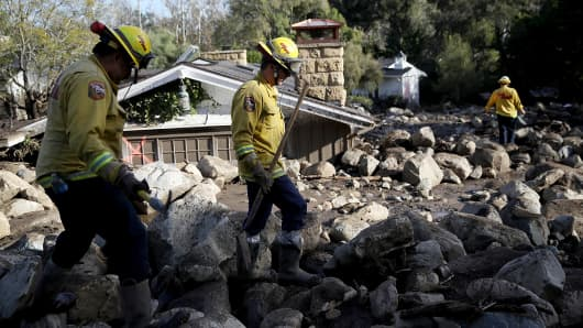 Firefighters search for people trapped in mudslide debris on January 10, 2018 in Montecito, California.