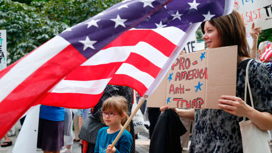 Protesters hold a placard reading 'Pro America - Anti-Trump'.