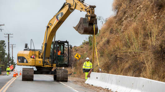 Traffic is diverted on Foothill Road as workers place K-rail barricades along burn areas during a winter rain storm in Ventura, California, January 9, 2018.