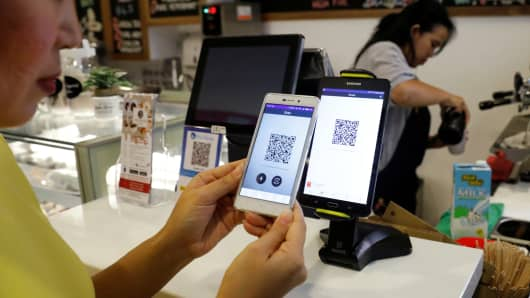 A woman pays for her coffee with cryptocurrency at Ducatus cafe, the first cashless cafe that accepts cryptocurrencies such as Bitcoin, in Singapore December 21, 2017.