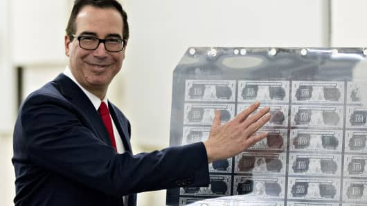 Steven Mnuchin, U.S. Treasury secretary, gestures while standing next to a printing plate for $1 dollar notes bearing Mnuchin's name at the U.S. Bureau of Engraving and Printing in Washington, D.C., U.S., on Wednesday, Nov. 15, 2017.