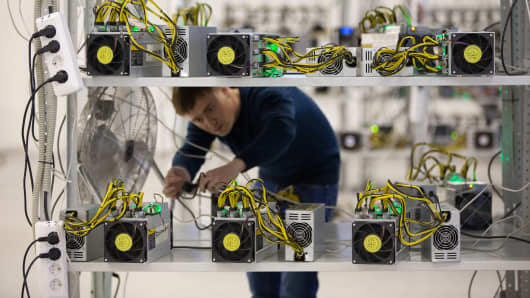 An employee checks power supply units and cooling fans used in cryptocurrency mining machine systems at the SberBit mining 'hotel' in Moscow, Russia, on Saturday, Dec. 9, 2017.