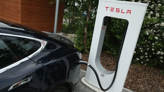 A Tesla electric-powered sedan stands at a Tesla charging station at a highway rest stop