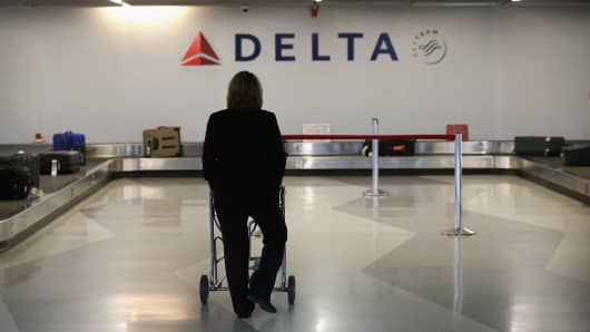 A passenger waits for her luggage in the Delta baggage claim at O'Hare International Airport on October 24, 2012 in Chicago, Illinois.