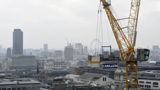 A construction crane showing the branding of British construction company Carillion is photographed on a building site in central London on January 14, 2018, with the skyline of the British capital in the background including the London Eye and the Houses of Parliament.
