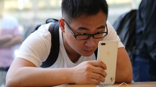 A man looks at iPhone 7 series product at an Apple store on September 16, 2016 in Beijing, China.