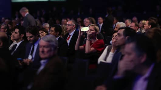 An attendee in the audience takes a photograph on a smartphone device during a special session at the World Economic Forum (WEF), in this photograph taken with a tilt-shift lens, in Davos, Switzerland, on Thur