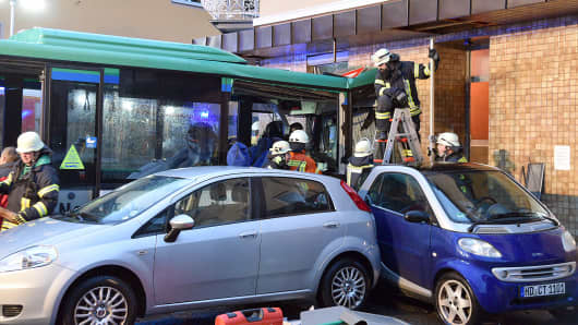 Police and firefighters secure the area around a schoolbus that crashed into a shop on early January 16, 2018 in the southern German town of Eberbach, near Heideleberg