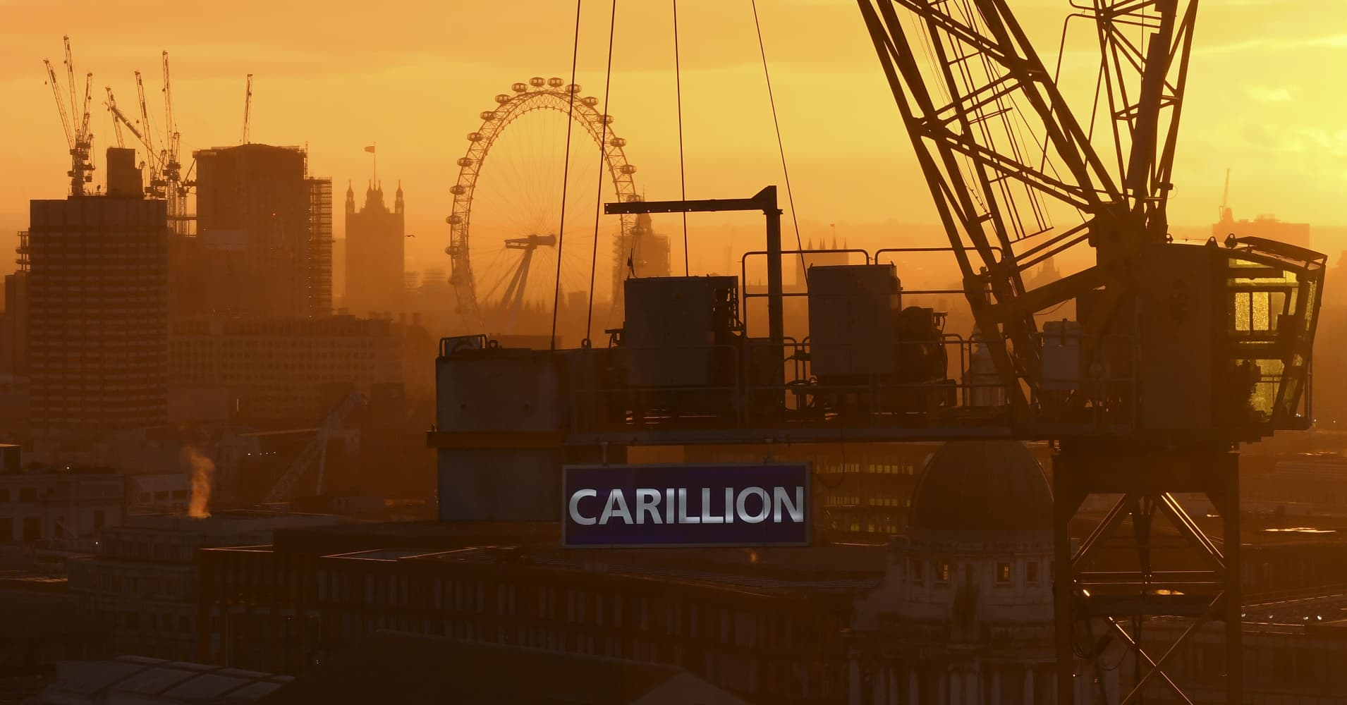 The sun sets behind a construction crane showing the branding of British construction company Carillion photographed on a building site in central London on January 15, 2018, with the skyline of the British capital in the background including the London Eye and the Houses of Parliament.