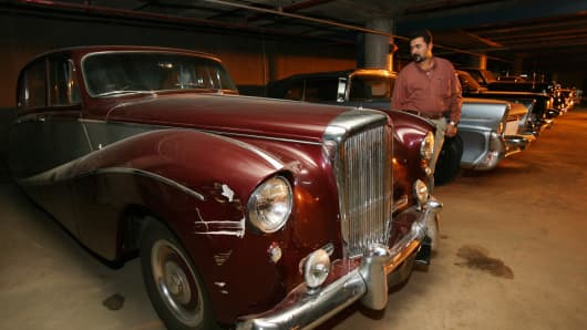 An Iraqi man inspects a classic car at a depot in Baghdad on March 19, 2008.