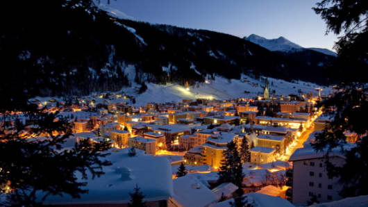 Snow-covered buildings stand illuminated at night in the town of Davos, the location for the World Economic Forum's (WEF)