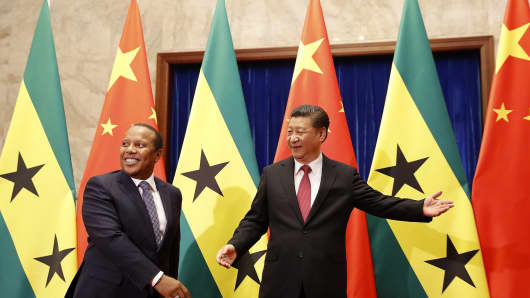 Chinese President Xi Jinping (R) shows the way to Sao Tome's Prime Minister Patrice Trovoada ahead of their meeting at the Great Hall of People in Beijing on April 14, 2017.
