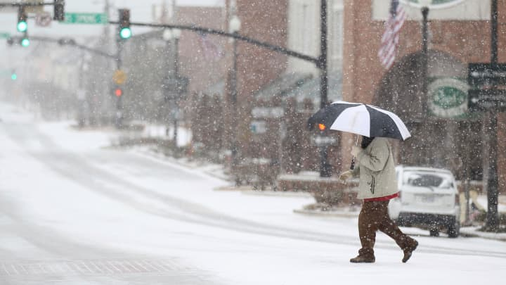 George Gilliam makes his way across West Main Street Tuesday, Jan. 16, 2018, in Tupelo, Miss., as he and few others brave the snow and wind to get around downtown.