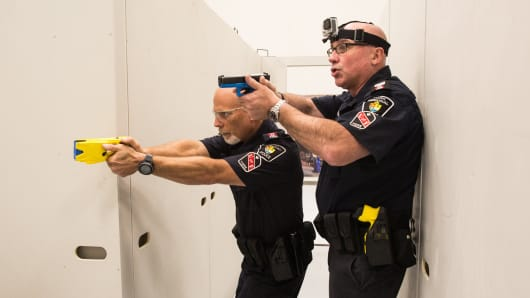 Police officers demonstrate de-escalation tactics and a taser deployment.