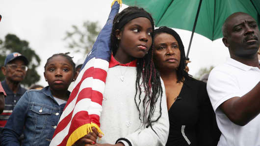 Erika Rigaud,15, holds an American flag as she joins with others to mark the 8th anniversary of the massive earthquake in Haiti and to condemn President Donald Trump's reported statement about immigrants from Haiti, Africa and El Salvador on January 12, 2018 in Miami, Florida.