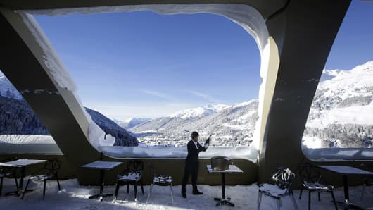 A hotel employee checks a bottle of champagne as he stands on the snow covered bar terrace of the InterContinental Hotel Davos
