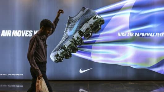 A pedestrian walks past an advertisement for Nike in Mumbai, India.