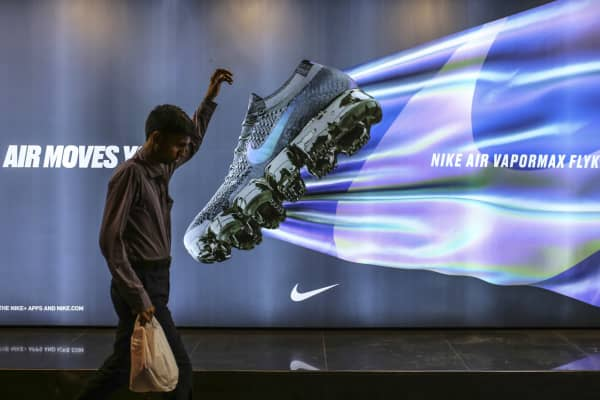 A pedestrian walks past an advertisement for Nike in Mumbai, India.