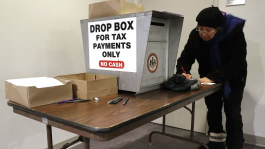 Residents fill out paper work and use locked drop boxes to pay their taxes at the Fairfax County Government Center December 28, 2017 in Fairfax, Virginia.
