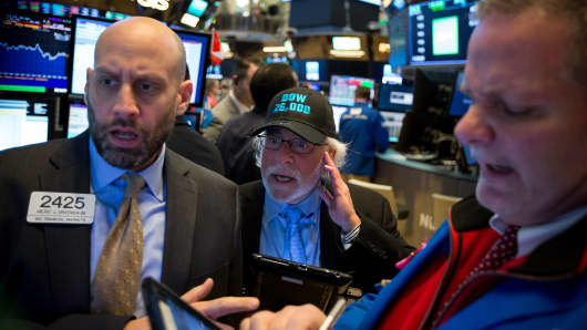 A trader wearing a 'Dow 26,000' hat works on the floor of the New York Stock Exchange (NYSE) in New York.