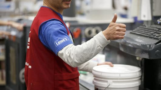 An employee prepares a paint order for a customer inside a Lowe's store in Burbank, California.